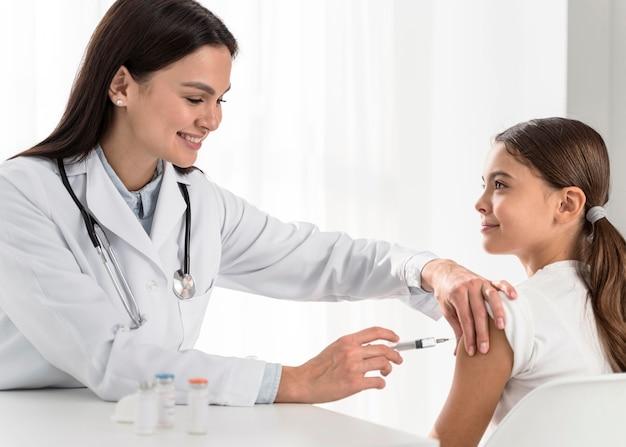 Petite fille regardant le médecin pendant qu'elle la fait vacciner