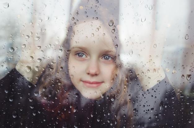 Petite fille regardant par la fenêtre