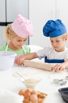 Petite fille en regardant son frère sérieux en utilisant un rouleau à pâtisserie