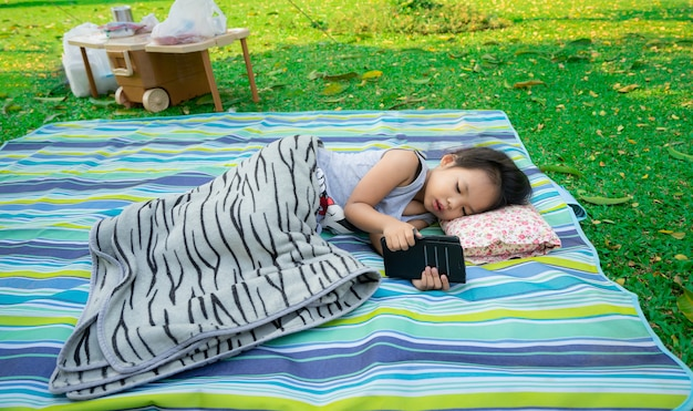 Petite fille en regardant un téléphone portable en position couchée dans le parc