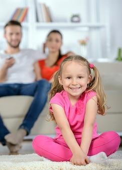 Petite fille en regardant la télévision avec les parents dans le salon