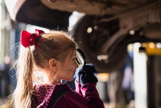 Petite fille regardant à travers la loupe