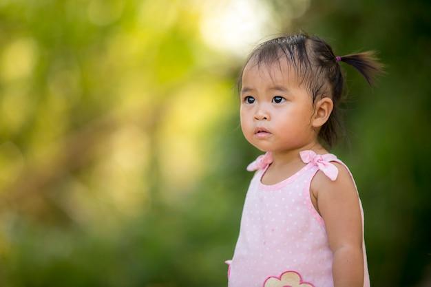 Petite fille, regarde l'avenir, la nature en arrière-plan