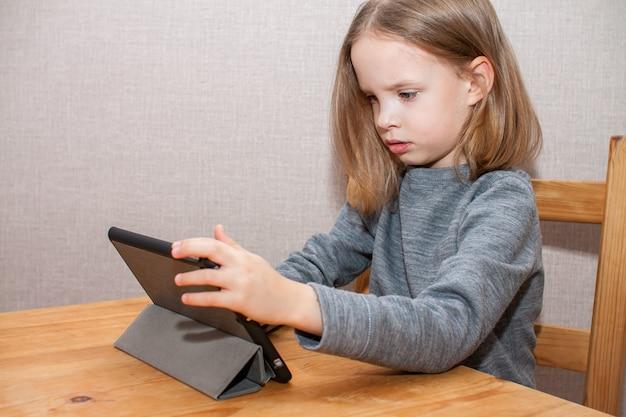 Petite fille regarde un didacticiel vidéo en ligne. formation à distance.