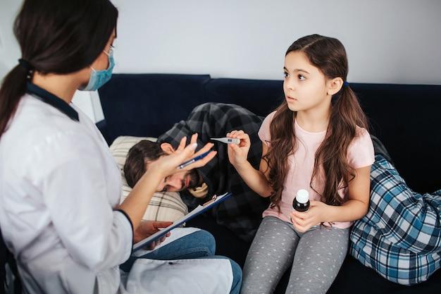Petite fille regarde femme médecin. elle tient un thermomètre et une bouteille de sirop. fille parle au médecin. jeune homme malade dormant sur le canapé. il a couvert d'une couverture.
