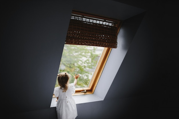 Petite fille regarde quelque chose dans la fenêtre