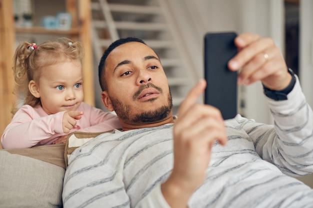 Petite fille, regarder, papas, smartphone