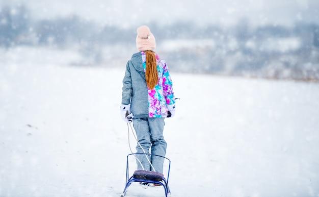Petite fille remontant la colline enneigée au cours d'une journée d'hiver enneigée