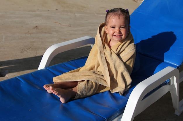 Petite fille repose assis sur une chaise près de la piscine