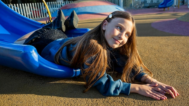 Petite fille restant au bord d'un toboggan