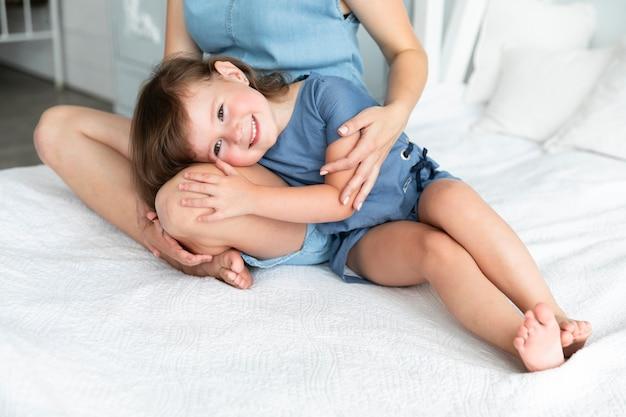 Petite fille reste avec sa tête sur les genoux de sa mère