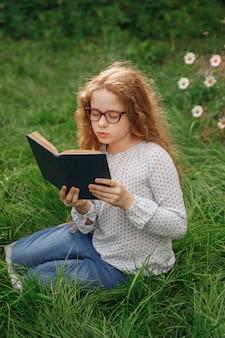 Petite fille rêver ou lire un livre en plein air. concept de l'éducation.