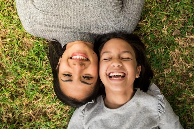 Petite fille riant avec sa mère couchée tête à tête sur l'herbe.