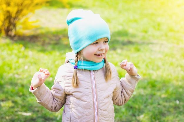 Petite fille en riant et souriant dans le parc sur l'herbe
