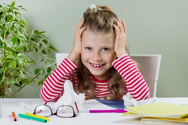 Petite fille rit, s'assied au bureau, dessine et écrit, les mains avec la tête.