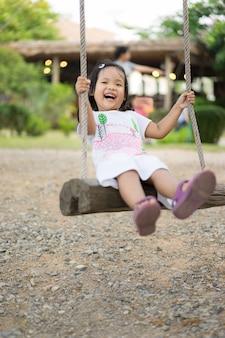 Petite fille en robe blanche assise sur une balançoire dans le parc