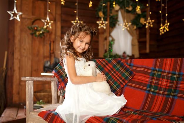 Petite fille en robe blanche assise sur le banc avec un lapin blanc