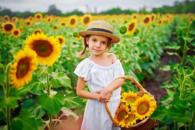 Petite fille en robe blanche, un chapeau de paille avec un panier plein de tournesols
