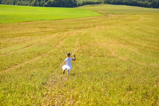 Une petite fille en robe blanche dans l'après-midi traverse le champ