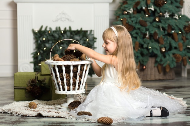 Petite fille en robe blanche joue avec des pommes de pin