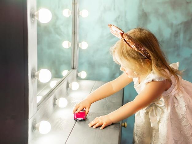 Petite fille en robe blanche joue avec la voiture de jouet.