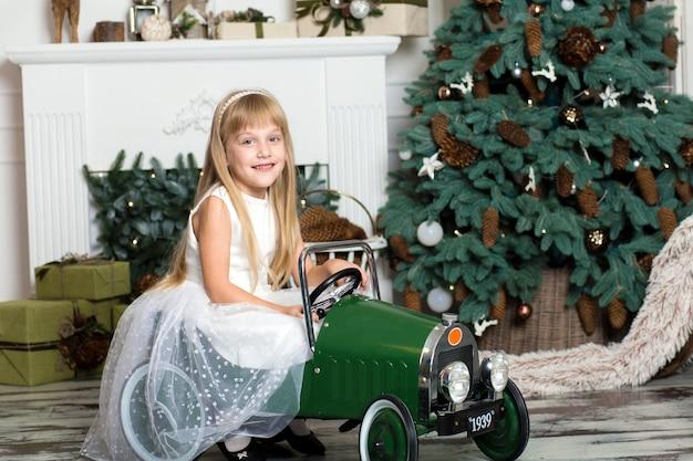 Petite fille en robe blanche monte une voiture vintage pour enfants dans des décorations de noël