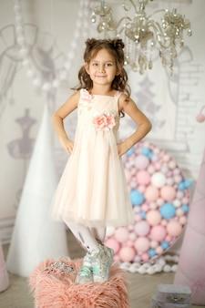 Petite fille en robe blanche posant comme une petite princesse
