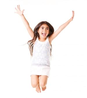 Petite fille en robe blanche posant en saut