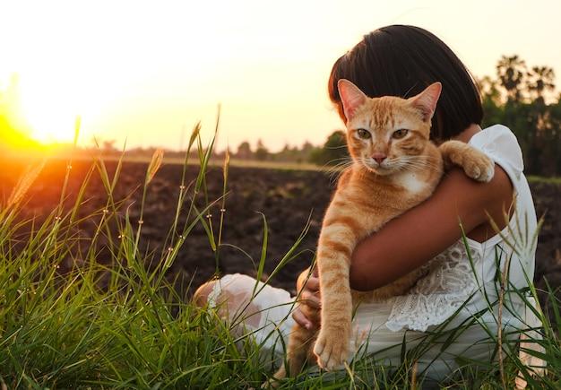Une petite fille en robe blanche se sentant détendue dans une belle prairie