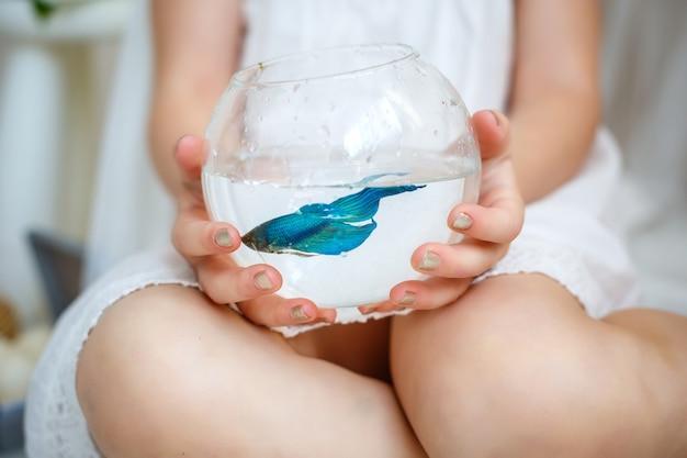 Petite fille en robe blanche tenant un aquarium avec des poissons bleus.
