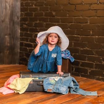 Petite fille en robe bleue et chapeau blanc ferme la valise avec des objets