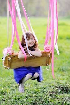 Petite fille en robe bleue à cheval sur une balançoire dans le cadre de verdure