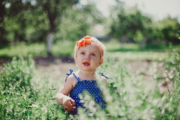 Petite fille en robe bleue dans un jardin ensoleillé