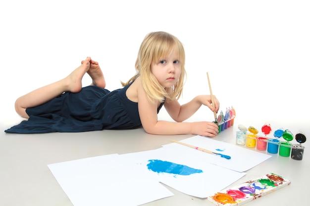 Petite fille en robe bleue dessine une peinture colorée