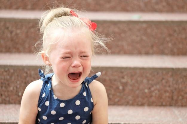 Une petite fille en robe bleue est assise sur les marches et pleure