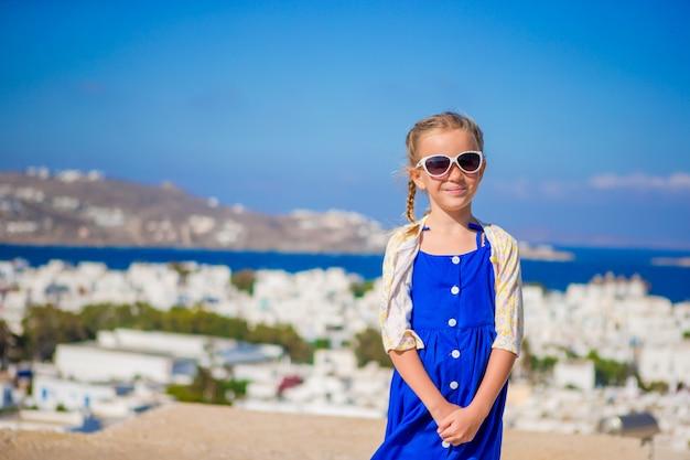 Petite fille en robe bleue à l'extérieur. enfant dans la rue d'un village traditionnel grec typique avec des murs blancs et des portes colorées sur l'île de mykonos, en grèce