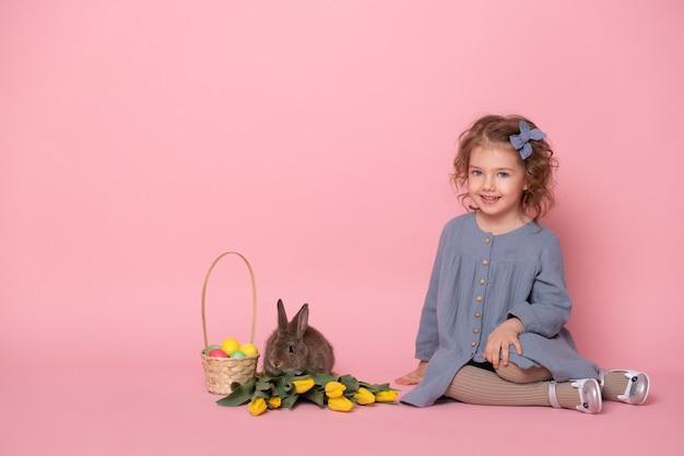 Petite fille en robe blu avec lapin, tulipes, panier avec des œufs colorés.