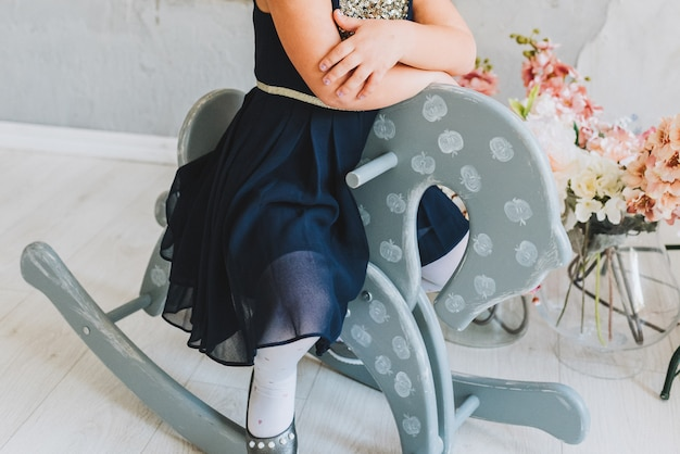 Petite fille en robe à cheval sur un cheval à bascule