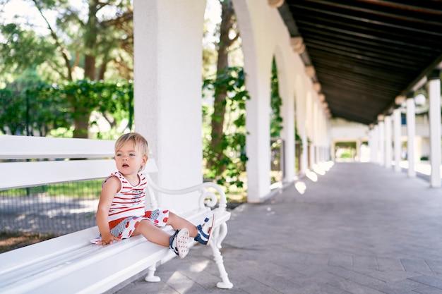 Une petite fille en robe est assise sur un banc blanc dans un pavillon du parc