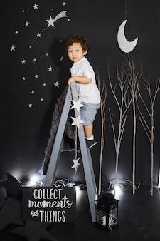 Petite fille en robe grise est assis sur une échelle dans la nuit petite fille rêvant