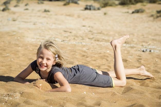 Petite fille en robe grise se repose sur le sable chaud.