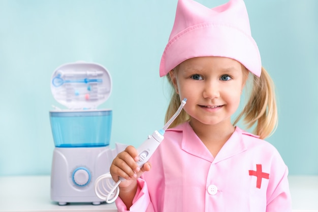 Une petite fille en robe d'infirmière se brosse les dents à l'aide d'un irrigateur. fille se brosse les dents avec un jet d'eau d'un irrigateur.