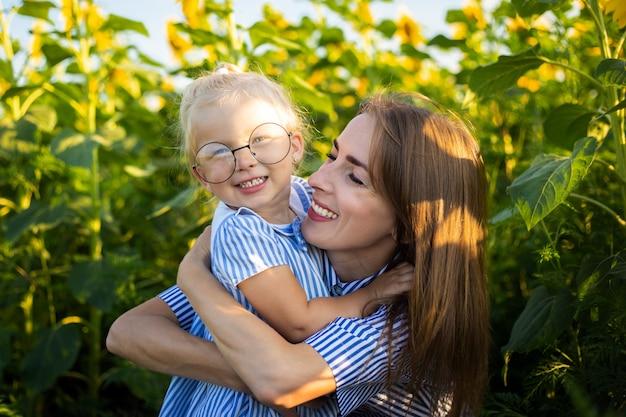 Petite fille en robe et lunettes et maman sur un champ de tournesol.