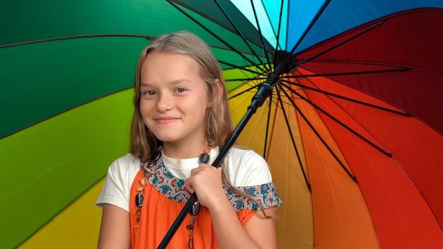 Petite fille en robe orange tenant un parapluie de couleurs arc-en-ciel debout applaudissant dans le studio à la recherche