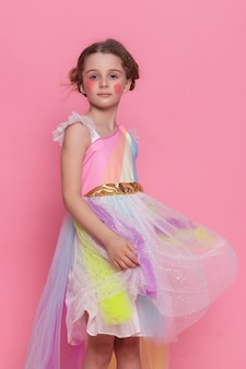 Petite fille en robe rose et chapeau d'anniversaire assis au sol avec de nombreux coffrets cadeaux, ballons à la maison, banderoles de fête d'anniversaire, joyeux anniversaire. célébrer