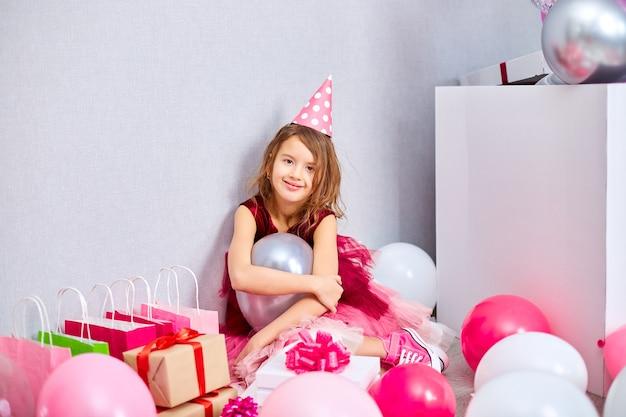 Petite fille en robe rose et chapeau d'anniversaire assis au sol avec de nombreux coffrets cadeaux et ballons
