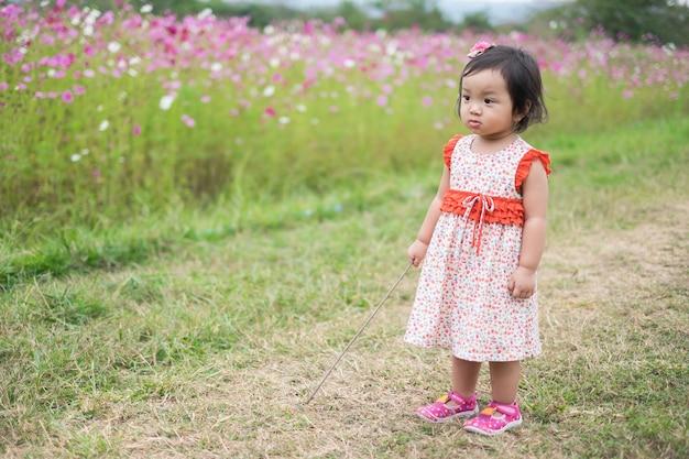 Petite fille en robe rose dans le jardin plein de fleurs