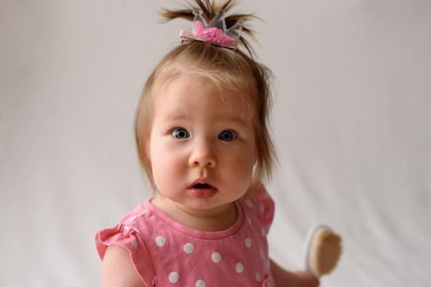 Petite fille en robe rose est assis avec un peigne à la main sur un mur blanc