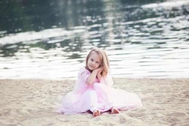 Une petite fille en robe rose est assise sur le sable, profitant de vacances d'été et d'un voyage en famille. repose sur la mer. enfants amusants. adorable jolie jeune fille jouant sur la plage au coucher du soleil