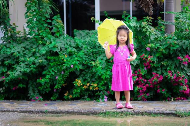 Petite fille en robe rose avec parapluie jaune pleut le jour